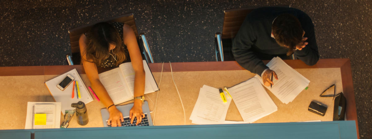 photo of 2 Boalt Hall students concentrating and frantically studying in library; materials and equipment scattered throughout